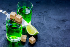Absinthe with sugar cubes in spoon on dark background mock up Royalty Free Stock Photos
