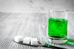 Absinthe with sugar cubes and spoon on wooden background. Close up Royalty Free Stock Image