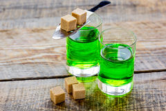Absinthe with sugar cubes in spoon on wooden background Stock Photo