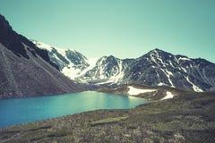 absolutamente liso espelho-como a superfície do lago das montanhas, céu nebuloso, costa da argila, montanhas distantes, contorno  fotos de stock royalty free