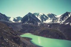 absolutamente liso espelho-como a superfície do lago das montanhas, céu nebuloso, costa da argila, montanhas distantes, contorno  imagem de stock royalty free