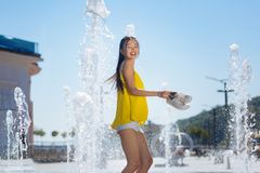 Joyful positive woman standing in the fountain barefooted. Absolute freedom. Joyful positive woman holding her shoes while standing in the fountain barefooted stock photos