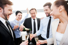 We absolutely deserve this!. Group of happy business people holding flutes while mature men pouring champagne royalty free stock photo