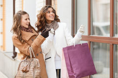 We absolutely need it! Two beautiful young women pointing the sh Royalty Free Stock Photo
