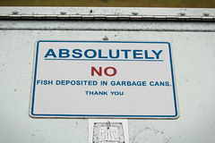 Absolutely no fish deposited in garbage can sign.  Royalty Free Stock Photography