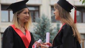 Absolvent in den akademischen Kleidern, die Diplome halten und nach Staffelung sprechen stock footage