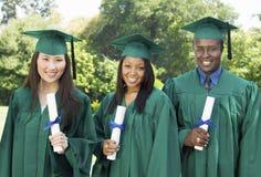 Absolwenci podnosi dyplomy na zewnątrz uniwersyteckiego portreta fotografia royalty free