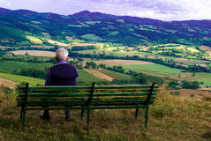 Absorbed in contemplation. An old man enjoyes in contemplation the beautiful landscape in front of him, Umbria Italy royalty free stock image
