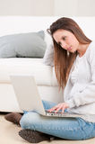 Absorbed young woman working on laptop Royalty Free Stock Photography