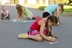 absorbedly孩子在路面的凹道白垩 免版税库存照片