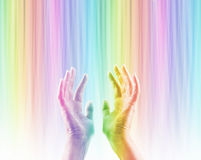 Absorbing Color Light Therapy. Female hands reaching up into rainbow colored light streaming down causing hands to become rainbow colored whilst absorbing the Royalty Free Stock Images