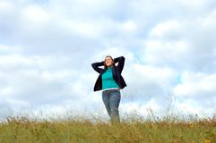 Absorbing nature. Female teen stands on the top of her world and absorbs the elements of nature around her Stock Image
