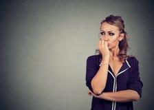 Absorbująca niespokojna kobieta gryźć jej paznokcie patrzeje strona Obraz Royalty Free