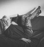 Absorption. Blond woman in black resting on black sofa stock photos