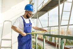 Abstandsmaß Arbeiten Sie an Standort, Arbeitskraft an der großen Höhe auf Baugerüst Stockbilder