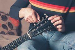 Abstimmende Gitarre des Mannes Lizenzfreie Stockfotografie