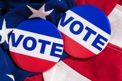 Abstimmungsknöpfe auf einem Hintergrund der amerikanischen Flagge Stockbilder