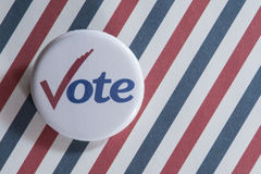 Abstimmungsknopf auf gestreiftem Hintergrund Stockfoto