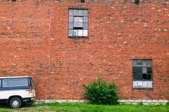 Abstract abandoned car and old red brick wall. An abstract image of an abandoned car and old red brick, abandoned warehouse wall with broken square windows Royalty Free Stock Photo