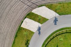 Abstract aerial view of the shadow of three trees standing at the edge of a curve on a path next to a field. Made with drone Stock Images