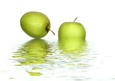 Abstract Apples. Abstract of two green apples with reflection in water, set against a white background Stock Photography