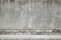Gray grungy concrete wall and tiled road Stock Photography
