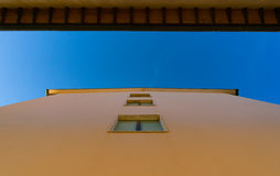 Abstract architectural background of yellow wall and blue sky Royalty Free Stock Image
