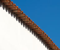 Abstract architecture. A simple image with only sky, wall and roof. This simplicity and symmetry makes this picture abstract, based on shapes and colors Stock Photo