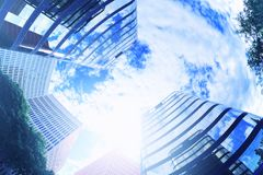Abstract architecture building with some skyscrapers from below. Cloud sky and sun flare. Empty copy space Royalty Free Stock Image