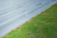 Abstract of architecture concrete staircase beside green grass meadow field at outdoor. royalty free stock photo