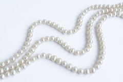Abstract arranged three rows of natural pale pearl necklace on white Stock Photos