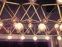 Abstract array of lamps. Abstract array of shining spherical lamps suspended from a golden structure Royalty Free Stock Image