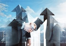 Teamwork and promotion concept. Abstract arrow handshake on city background. Teamwork and promotion concept. Double exposure stock photo