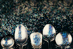 Abstract art concept with multicolored glitter and spoons. Idea of the sky, space, music and subcultures. Background. Royalty Free Stock Photo