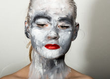 Abstract art makeup. Face and neck girls smeared with gray colors and bright red lips. Holi Festival.  stock images