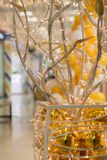 Abstract artificial tree of metal tubes, garlands and yellow balls Stock Images