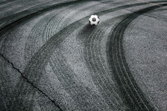 Abstract asphalt tires tracks with soccer ball Royalty Free Stock Photography