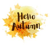 Abstract autumn background. With orange falling maple leaves. `Hello autumn` lettering and yellow watercolor blots Royalty Free Stock Images
