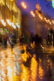 Abstract background of blurred people figures under umbrellas, city street in rainy evening, orange-brown tones. Bright reflections of street lamps in the wet Royalty Free Stock Photos