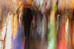 Abstract background of blurred people hurrying down the city street under umbrellas in rainy evening, Impressionism. Style, colorful lighting. Intentional Stock Photography