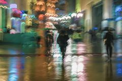 Abstract background of blurred people under umbrellas hurrying down the city street in rainy evening, impressionism. Style, colorful lighting. Intentional stock photography