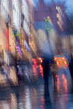 Abstract background of blurred Woman with girl under umbrella, city street in rainy. Intentional motion blur. Abstract background of blurred people figures under Stock Image