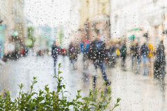 Abstract background of blurred young people walking down the street in rainy day. Raindrops on window glass. Intentional. Motion blur. Concept of seasons Stock Photography
