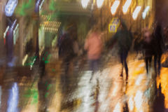 Abstract background of blurred young people walking down the street in rainy evening, Impressionism style, colorful Stock Photography