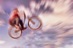 Abstract background. Boy on a BMX mountain bike jumping. Motion Stock Images