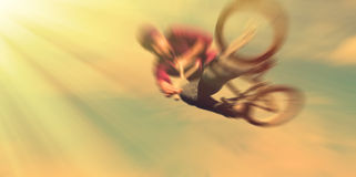 Abstract background.  Boy on a BMX mountain bike jumping. Motion Stock Image