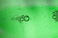 Abstract background from bubbles of carbonated water through a green glass bottle Stock Images