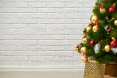 Abstract background from christmas tree and blank brick wall, classic white interior backdrop, copy space for text, winter holiday Stock Photo