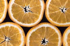 Abstract background with citrus-fruit of orange slices. Dark background. Close-up. Studio photography. Royalty Free Stock Image