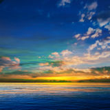 Abstract background with clouds and sea sunrise. Abstract blue nature background with clouds and golden sea sunrise Stock Images